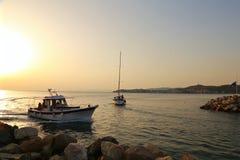 游艇在从小游艇船坞的海漂浮在日落 免版税库存图片