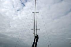 游艇帆柱和索具反对阴暗天空的 库存照片