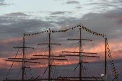 游艇帆柱在日出的在高石牌的结局的口岸 库存照片