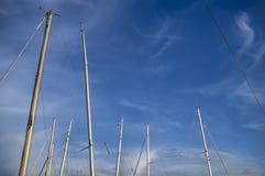 游艇帆柱在阳光下反对蓝天和云彩 免版税库存照片
