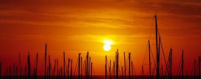 游艇帆柱,在口岸的红色日出剪影  库存照片