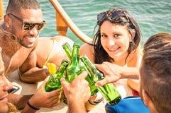 游艇的多种族人一起喝-小组朋友的 图库摄影