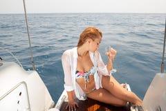 游艇的美丽的妇女与杯酒 免版税库存照片