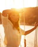 游艇的美丽的妇女在日落 免版税图库摄影