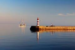 游艇航行通过与灯塔的防堤 库存照片