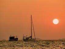 游艇Defocus在日落的海 现出轮廓小船在海的日落有橙色天空的在背景中 免版税库存图片