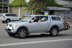 游行挥动的旗子的成员从汽车的 免版税库存照片