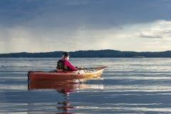 游览检查天气预报斯德哥尔摩群岛的划皮船的妇女 免版税库存图片