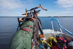 游览自行车安全地被栓对在湖Saimaa的一个渔船,芬兰 免版税库存图片