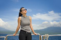 游览船或轮渡的年轻可爱和愉快的亚裔中国妇女享用在暑假海船旅行的海风 库存照片