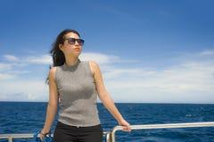 游览船或轮渡的年轻可爱和愉快的亚裔中国妇女享用在暑假海船旅行的海风 免版税库存图片