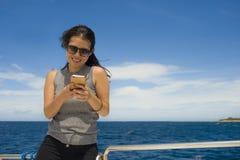 游览船或轮渡的年轻可爱和愉快的亚裔中国妇女使用互联网手机微笑在假日小船的 图库摄影