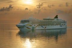 游轮挪威之光号进入百慕大的港在日出 免版税库存照片