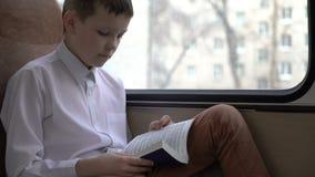 游遍乘公共汽车的一位年轻男小学生的射击城市和读一本书 股票录像