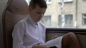 游遍乘公共汽车的一位年轻男小学生的射击城市和读一本书 影视素材