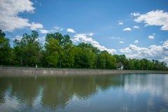 湖、一个美妙的绿色森林和一个老房子的岸的一个美丽的公园 图库摄影