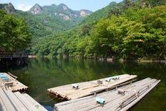 湖、山和竹子木筏 免版税库存图片