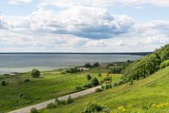 湖、空的路、小山和平原 免版税库存图片