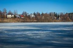 冻湖与一个村庄的早期的春天在背景中 免版税图库摄影