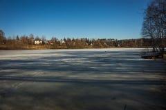 冻湖与一个村庄的早期的春天在背景中 库存图片