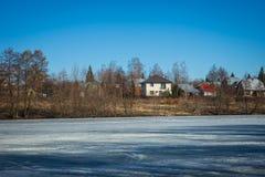 冻湖与一个村庄的早期的春天在背景中 免版税库存照片