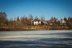 冻湖与一个村庄的早期的春天在背景中 库存照片