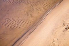 湖到达的含沙岸顶视图透明波浪  免版税库存照片