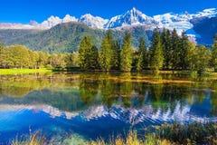 湖反射了积雪覆盖的阿尔卑斯和常青云杉 库存照片
