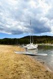 湖和一艘皮船停泊的两条游艇支持 免版税库存照片