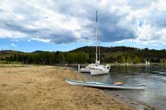 湖和一艘皮船停泊的两条游艇支持 免版税库存图片
