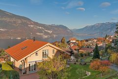 湖图恩,瑞士- 2015年10月27日:湖图恩和在烟特勒根附近镇的典型的瑞士村庄秋天视图  库存照片