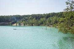 湖在一个森林里用反对背景的清楚的绿松石水 库存照片