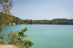 湖在一个森林里用反对背景的清楚的绿松石水 库存图片