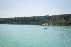 湖在一个森林里用反对背景的清楚的绿松石水 免版税库存照片