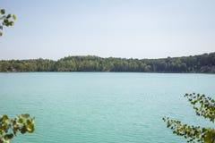 湖在一个森林里用反对背景的清楚的绿松石水 图库摄影