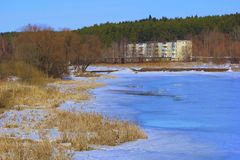 冻湖在冬天和一个小镇 库存图片