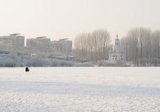 冻湖在有渔夫的城市房子和教会背景的  图库摄影