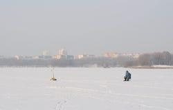 冻湖在有渔夫的城市房子和教会背景的  免版税库存图片