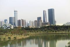 湖在青山和摩天大楼背景  美好的都市风景 图库摄影