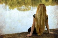 湖孤独的副坐的孑然妇女 免版税库存图片
