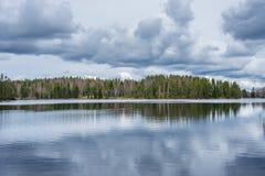 湖岸的森林有上面多云天空的,反映在水 库存照片