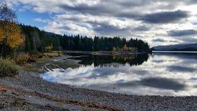 湖平安和安静的风景有在镇静水和秋天树反映的剧烈的云彩的  库存图片