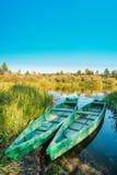 湖或河和两个老木蓝色划船渔船美好的夏天晴天或  免版税库存图片