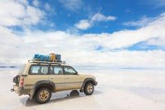 湖撒拉族de Uyuni被反射的表面上的越野汽车在玻利维亚 库存图片