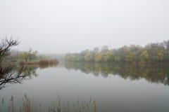 湖有薄雾的早晨 在这个湖的一场厚实的清早雾 免版税库存照片