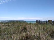 湖水蓝色灯塔码头天空海滩沙丘沙子漂流木头日志岩石小卵石旅行冒险密执安湖 库存图片