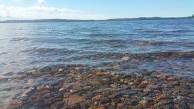 湖清楚的水 做下面一块美丽的石头 图库摄影