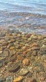 湖清楚的水 做下面一块美丽的石头 库存图片