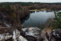 湖的可爱的看法有鲜绿色小山的,围拢由峭壁 这里没人 森林反射在水中 图库摄影