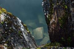 湖的可爱的看法有鲜绿色小山的,围拢由峭壁 这里没人 森林反射在水中 免版税库存照片